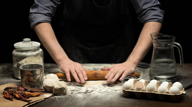 Chef hands are rolling dough on wooden table