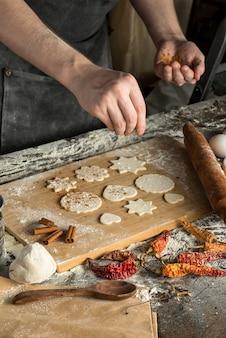 요리사의 손에 나무 보드, 근접 세로보기에 원시 쿠키에 계피를 뿌린다