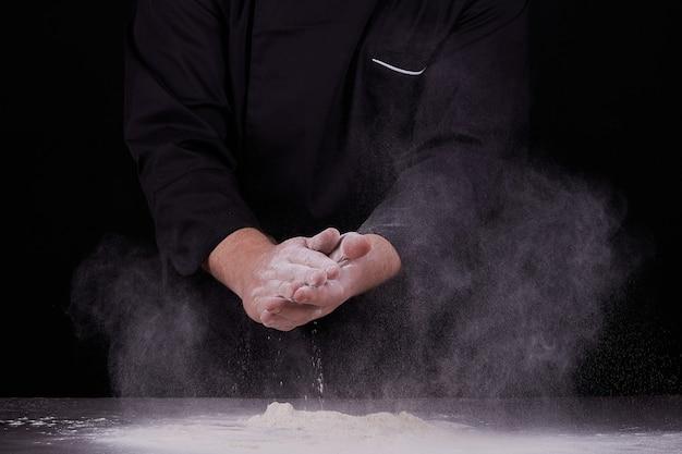Шеф-повар хлопает в ладоши и белой мукой на черном