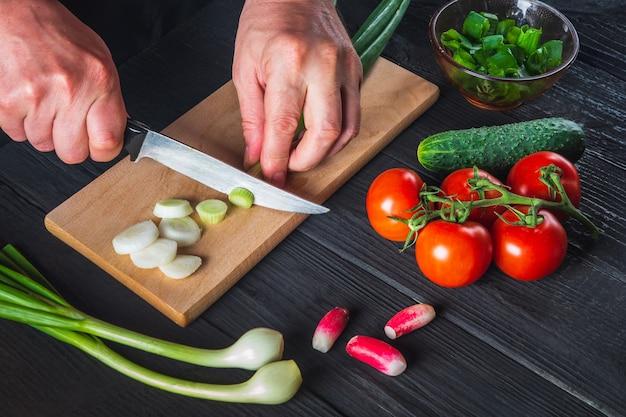 요리사 손 클로즈업은 젊은 파를 잘라냅니다. 레스토랑 주방에서 요리 샐러드. 샐러드 다이어트를 위한 야채 세트입니다.