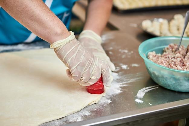シェフは、テーブルの上に小麦粉をまぶした手作りのラビオリとヒンカリをまな板の背景に餃子を調理します。おいしい自家製料理。