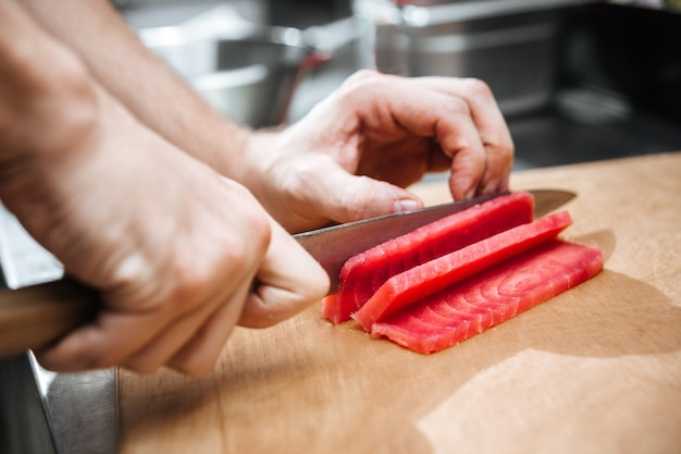 Chef hands cut tuna into slices on a wooden board
