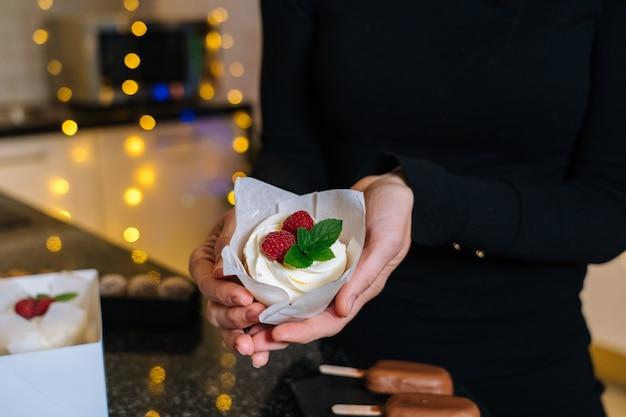 シェフの手は、フルーツと自家製のクリスマスカップケーキを保持しています。明けましておめでとうございます。