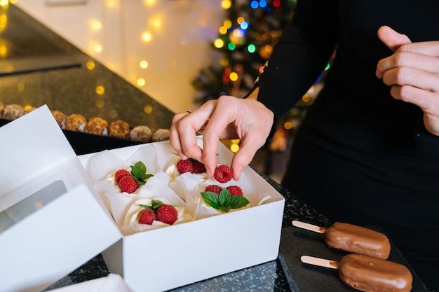 シェフの手が自家製のクリスマスフルーツケーキを持っています。明けましておめでとうとメリークリスマスの背景