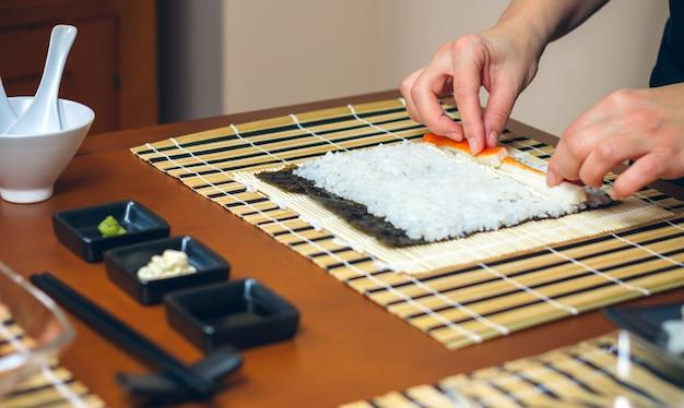 シェフが手でご飯に具材をのせて寿司を作る