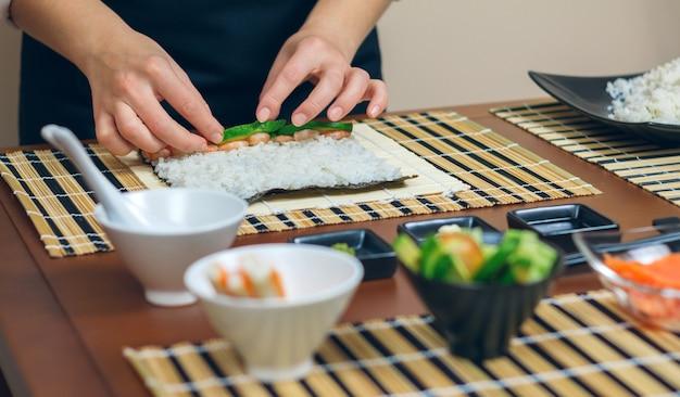 Руки повара кладут ингредиенты на рис, чтобы приготовить суши