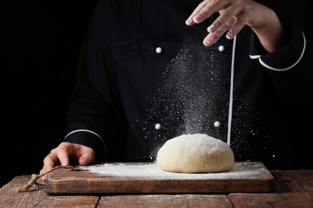 Chef hands pouring flour powder on raw dough.