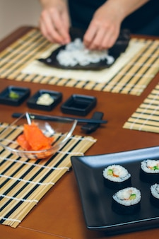 Chef hands preparing sushi with plate of finished maki rolls