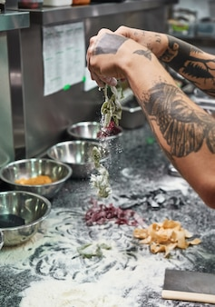 Chef hands with tattoos making traditional italian pasta in restaurant kitchen