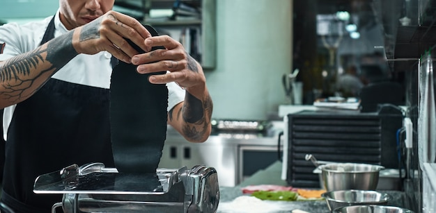 Chef hands with tattoos rolling a black dough through pasta machine in the kitchen