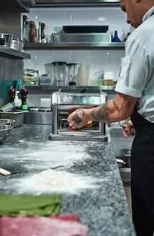 Руки шеф-повара с татуировками раскатывают тесто через макаронную машину на кухне ресторана
