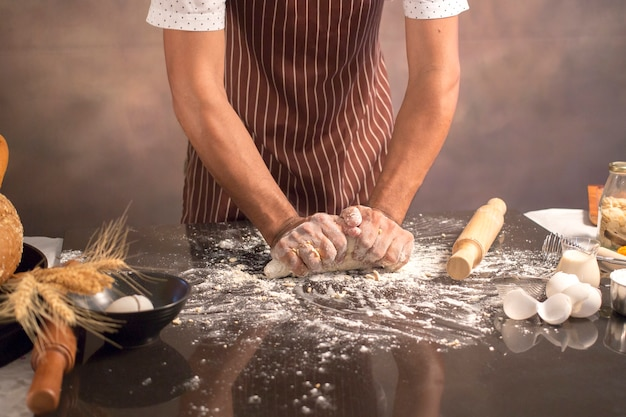 Chef hipster stylish kneads dough for bread on wooden board