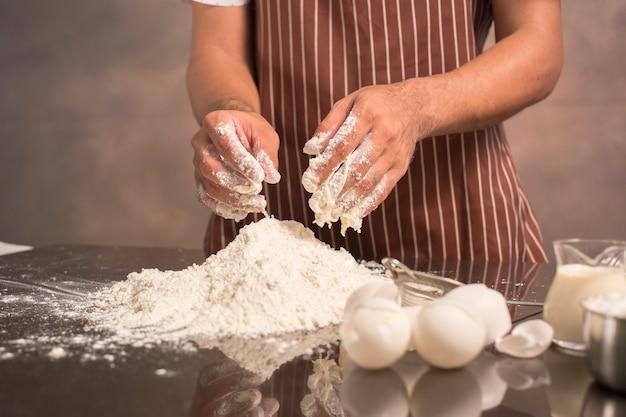 Шеф-повар hipster стильный месит тесто для хлеба на деревянной доске