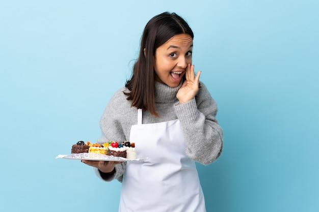 製品を紹介するために側面を指している大きなケーキを持ってシェフが何かをささやく