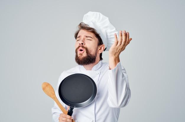 フライパンを持ったシェフが料理の台所用品レストランを準備しています。高品質の写真