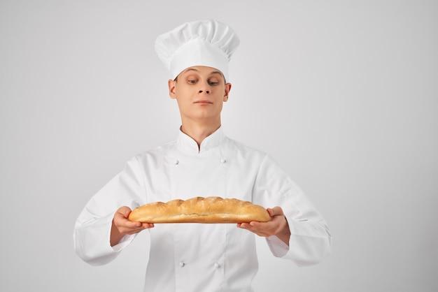 Шеф-повар держит в руке буханку свежего продукта. профессиональный пекарь. фото высокого качества