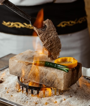 Chef holding beef steak on stone with grilled peppers on fire