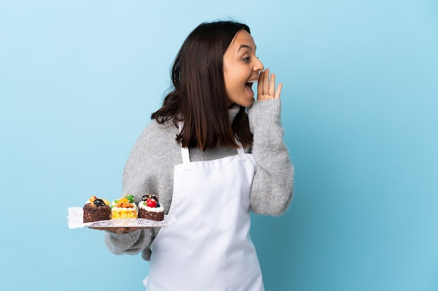 Chef holding a big cake shouting with mouth wide open to the side