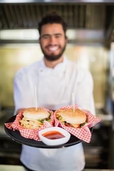 シェフが商業kitchencでプレートにハンバーガーを保持