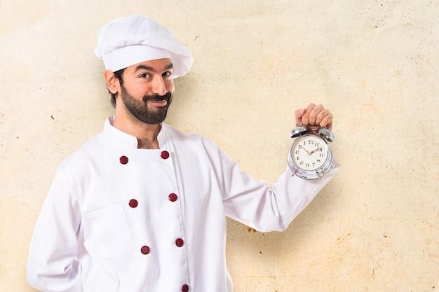 Chef in possesso di un orologio su sfondo bianco