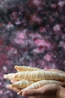 Cuoco unico che tiene i biscotti croccanti con zucchero in polvere in mano.