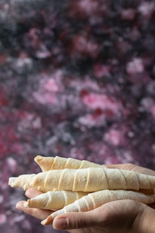 Шеф-повар держит в руке хрустящее печенье с сахарной пудрой.