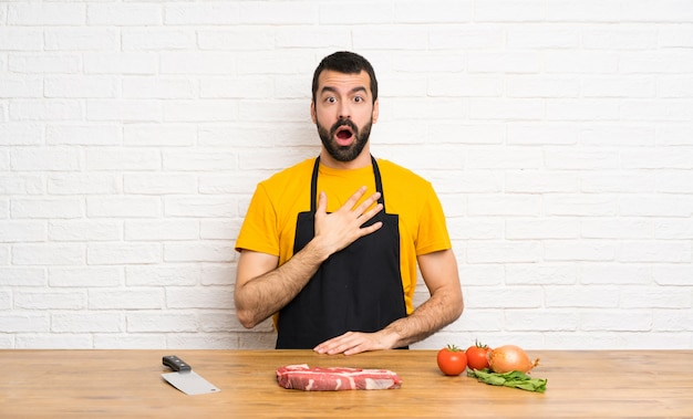 Chef holding in a cuisine surprised and shocked while looking right