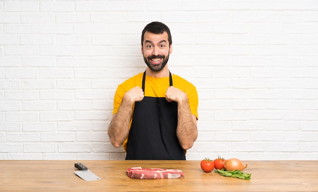 Chef holding in a cuisine with surprise facial expression