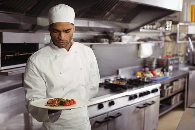 シェフがキッチンでおいしい料理を保持