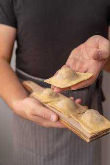 Шеф-повар держит в руке макароны с начинкой