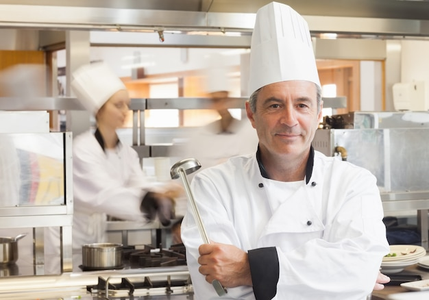 Chef holding ladle while smiling