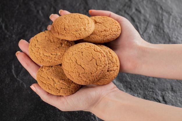 Un cuoco unico che tiene i biscotti della farina d'avena nella mano.