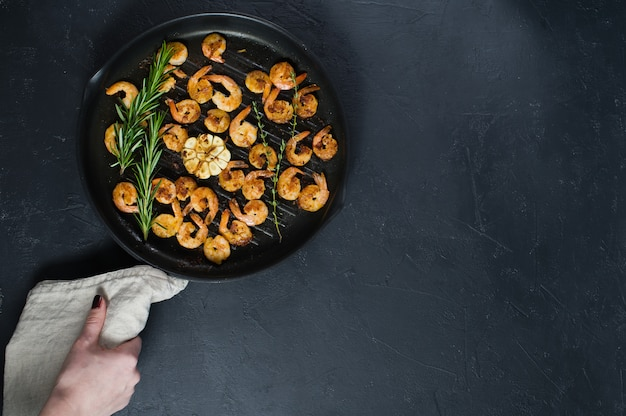 Chef holding pan with fried shrimps.