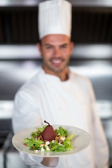 Chef holding plate in kitchen