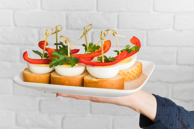 Chef holding plate with bruschettas