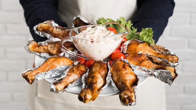 Chef tenendo la piastra con pollo