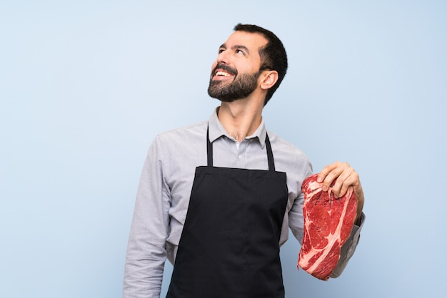Chef holding a raw meat happy and smiling