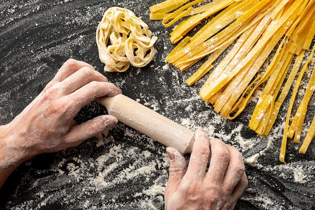Chef holding rolling pin near pasta