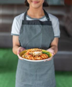 Шеф-повар держит жареную лапшу с креветками