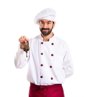 Chef holding vintage padlock over white background