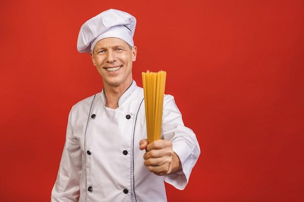Шеф-повар держит кучу спагетти в руках. catering и итальянская концепция еды изолированные на красной предпосылке. повар с довольным лицом в белой униформе держит сухие макароны. Premium Фотографии