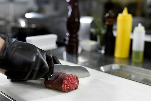 Chef in hotel or restaurant kitchen cooking, only hands, he is cutting meat or steak