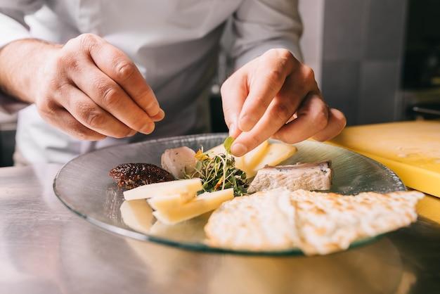 Шеф-повар в ресторане украсит сырную тарелку зеленью и хлебом