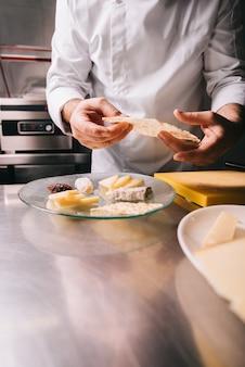 Шеф-повар в ресторане украсить сырной тарелкой