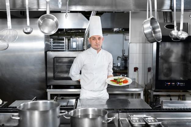 레스토랑에서 요리사는 기성품 요리와 함께 접시를 보유