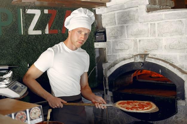 白い制服を着たシェフがピザを準備します