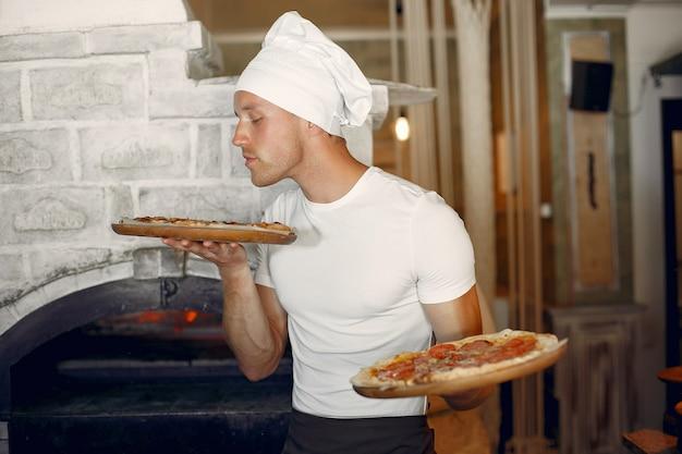 흰색 유니폼을 입고 요리사는 pizzaa를 준비
