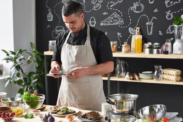 주방에서 자신의 휴대 전화로 접시에 자신의 특별한 요리를 촬영하는 앞치마 요리사