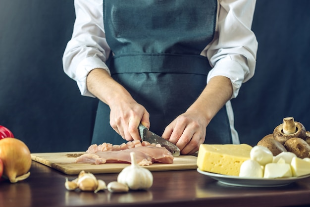 Шеф-повар в черном фартуке режет куриное филе
