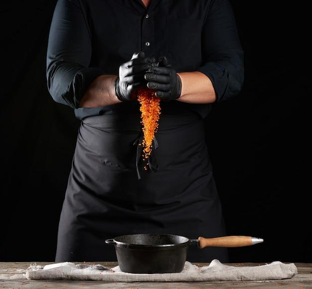 黒い服を着たシェフとラテックスの手袋が生のレンズ豆を丸い鋳鉄製の鍋に注ぐ
